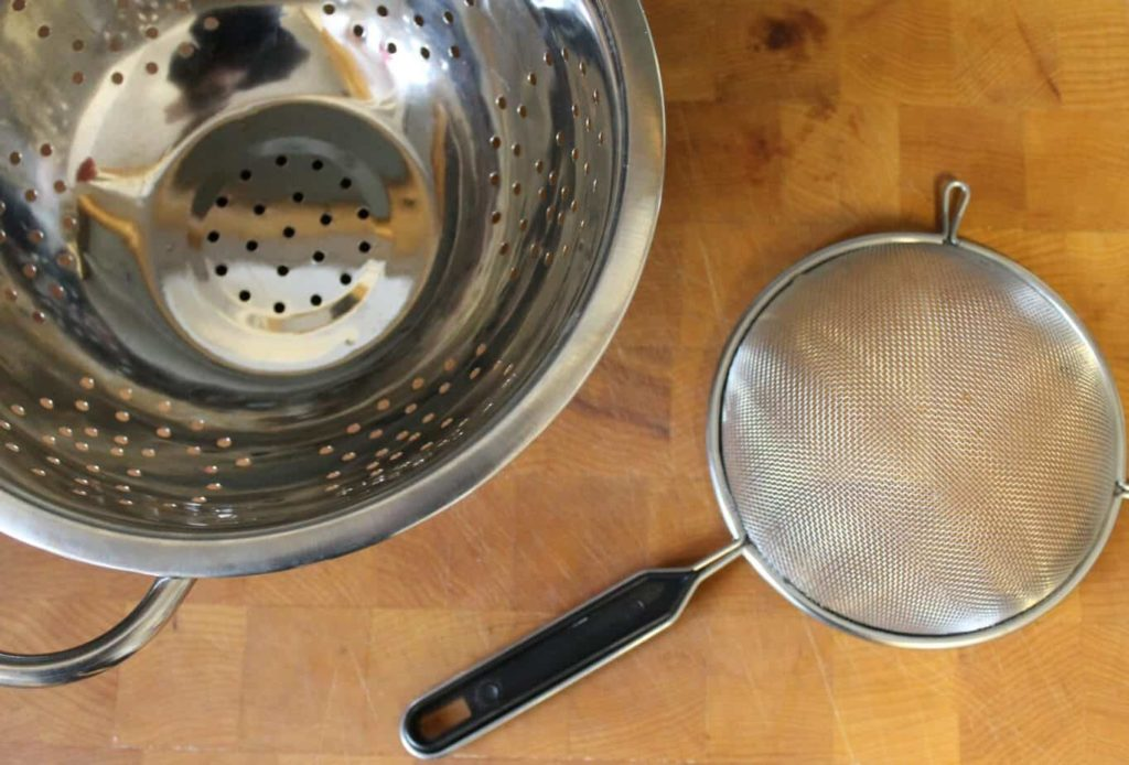 examples of a colander and sieve on a wooden background