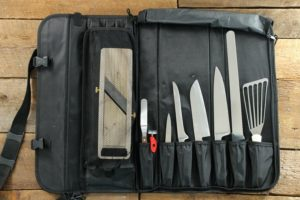 A knife roll filled with different types of kitchen knives on a wooden tabletop