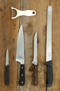 vertical image of a paring knife, chefs knife, boning knife, and serrated slicer on a wooden table top