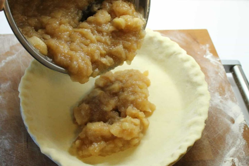a unbaked pie shell being filled with homemade apple pie filling