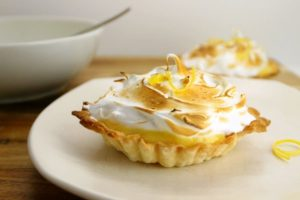 2 lemon meringue tarts on plates