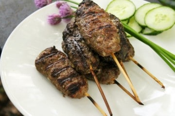 a white plate with frilled beef kofta kebabs stacked on it