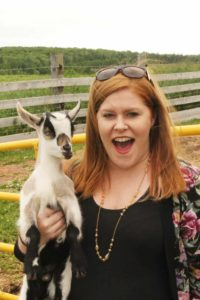 Stephanie holding a baby goat at Island Hill Farm in PEI.