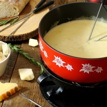 a red caquelon filled with real swiss cheese fondue on a wooden board surface surrounded by various ingredients