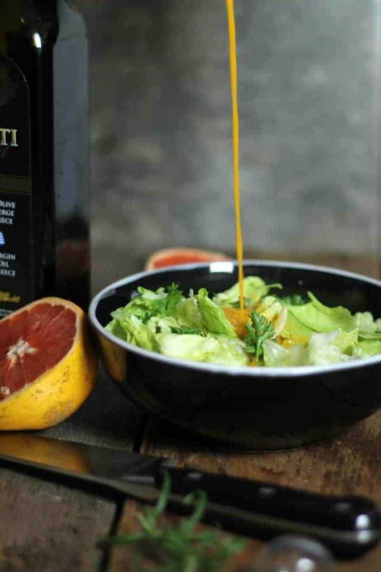 A stream of grapefruit vinaigrette being poured into a black bowl filled with salad greens