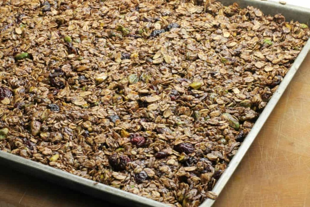 Homemade granola bar mixture spread on a sheet pan before baking at 300F for 30 minutes.