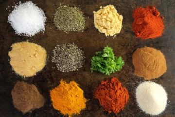 various essential spices in little piles on a dark background