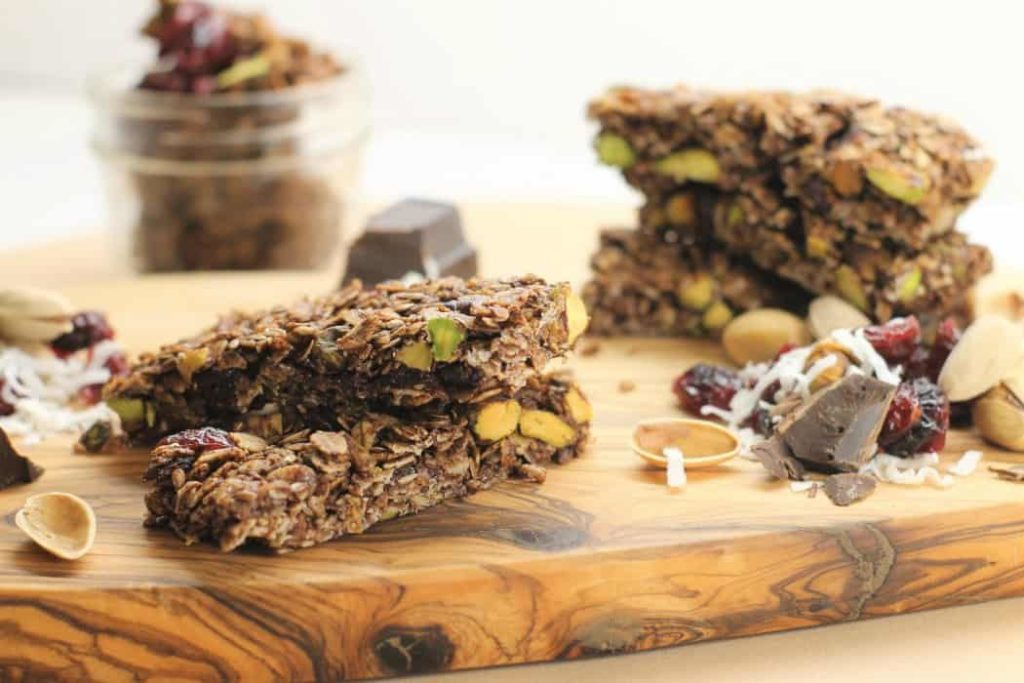 Homemade gluten free Granola Bars on a wooden board surrounded by various ingredients
