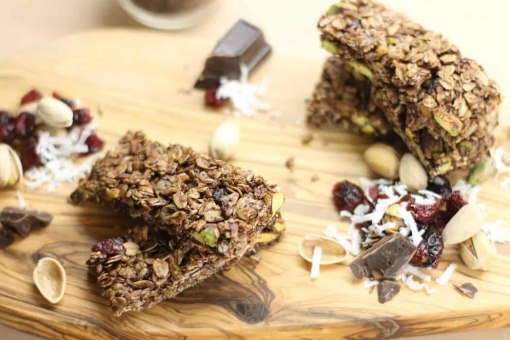 Pistachio, Cocoa, and Cherry stuffed homemade Granola Bars on a wooden board