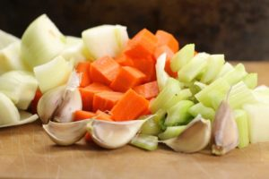 a Mirepoix mix on a wooden cutting board, a simple vegetable mix used in making stocks and broths