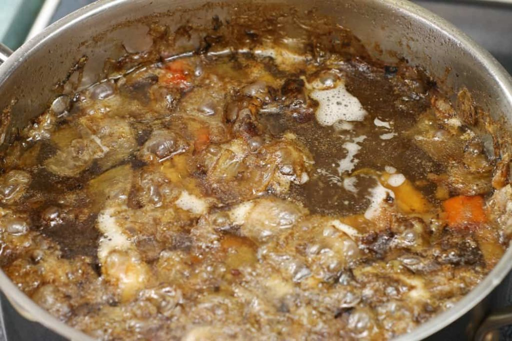 A beef stock simmering away on the stove top
