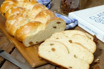 sliced german rosinenbrot (raisin bread) displayed on a wooden cutting board, and surrounded by ingredients and a cookbook