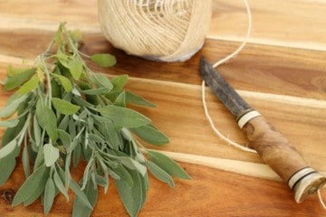 a bunch of sage on a wooden board with twine and a knife