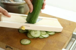 Use a mandolin slicer to cut the cucmbers quickly and easily for this gurkensalat recipe.
