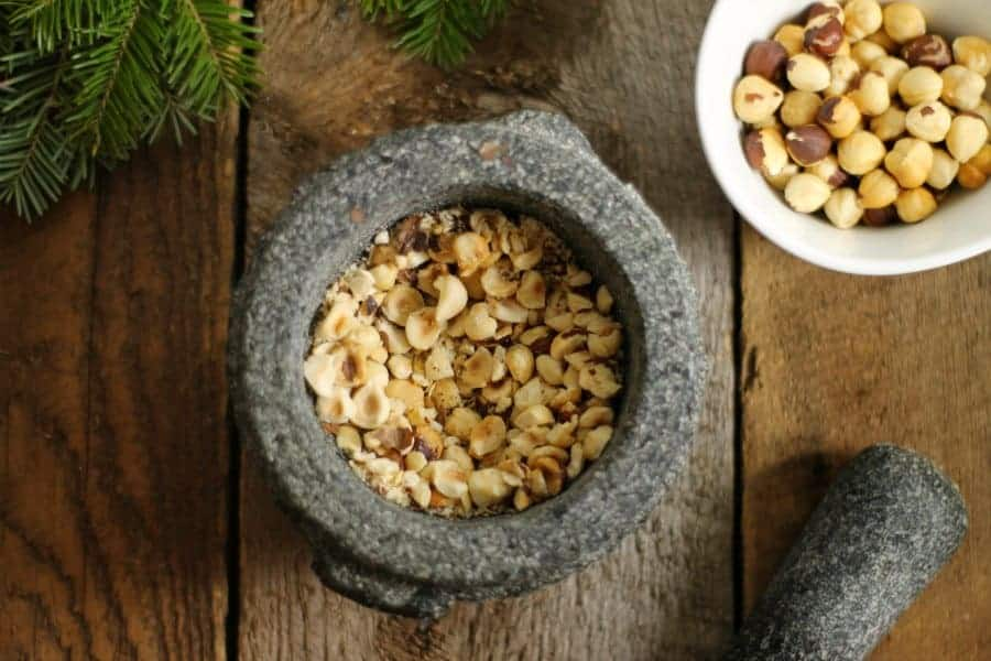 A bowl of crushed toasted hazelnuts in a mortar and Pestel on a barn board background