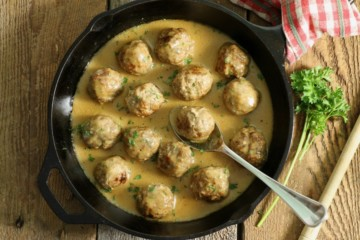 a cast iron pan filled with gluten free swedish meatballs on a barn board back board