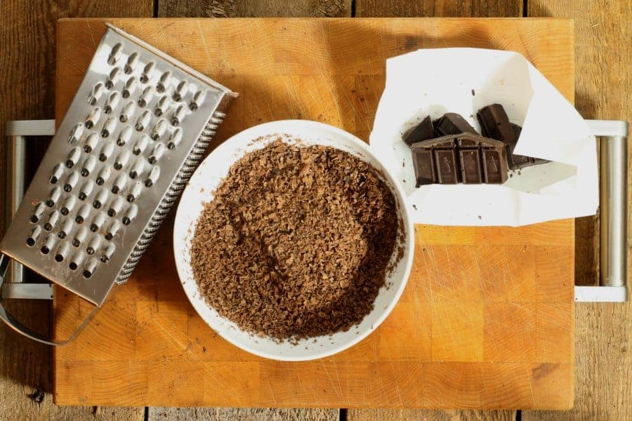 A box grater , white bowl, and dark bakers chocolate laying on a wooden cutting board. The bowl is filled with freshly grated chocolate shavings.