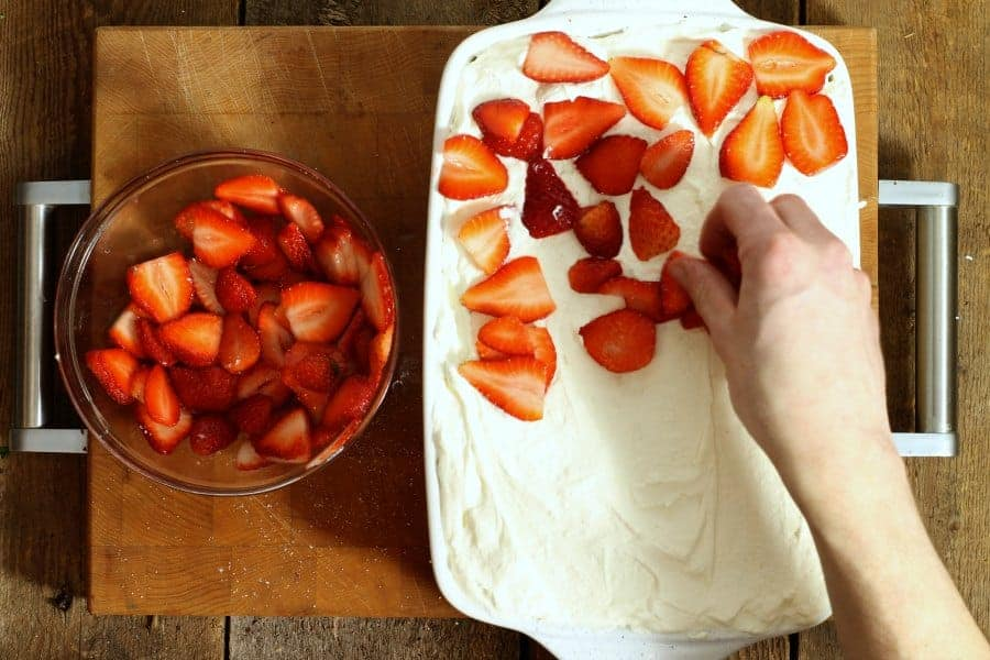 Layering sliced macerated strawberries on top of mascarpone cream for the strawberry tiramisu