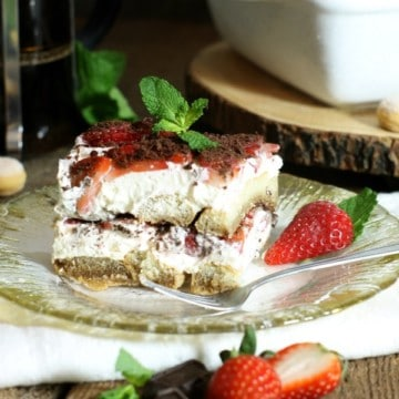 A square piece of strawberry tiramisu in a glass plate, sitting on a white napkin.
