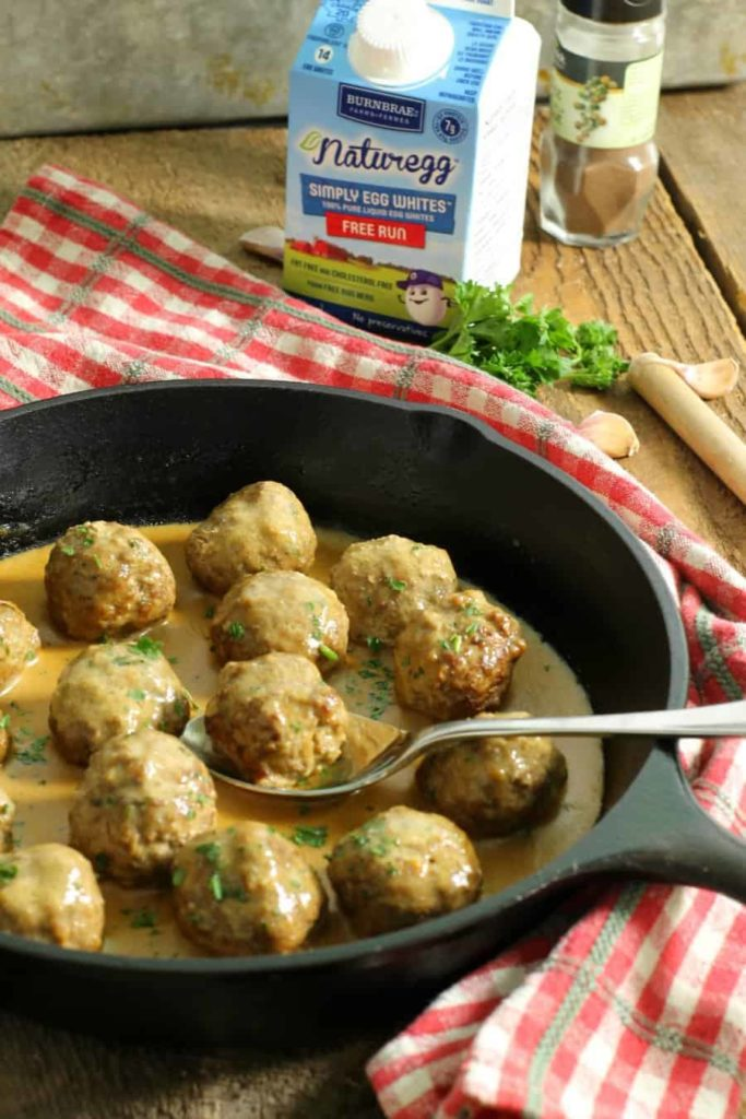 Gluten free swedish meatballs in a cast iron pan with a red checkered cloth wrapped around the handle.