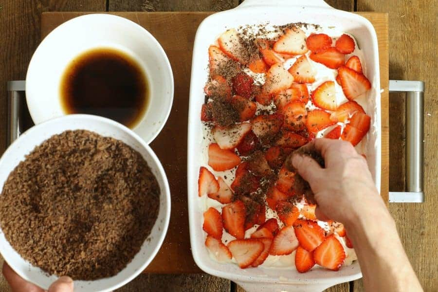 Sprinkling grated dark chocolate shavings over top of the strawberry tiramisu as garnish