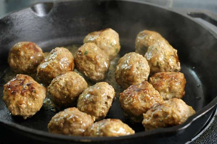 swedish meatballs in a cast iron pan being cooked