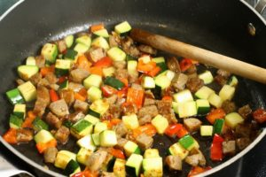 Diced sausage, zucchini, and red bell pepper being sauteed in a pan.