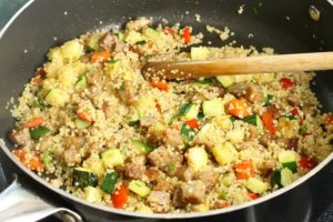 A quinoa and sausage stuffing being mixed in a large frying pan