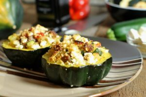 Two acorn squash stuffed with a quinoa and sauasage stuffing baked and topped with cheese
