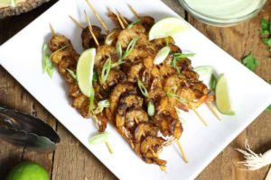 blackened shrimp skewers on a white platter with various garnishes