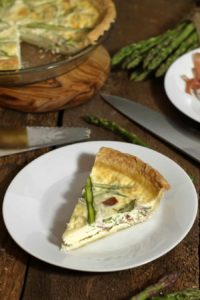 a top down view of a piece of prosciutto and asparagus egg white quiche