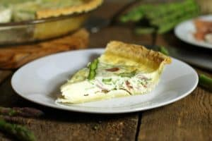 a slice of asparagus quiche on a white plate