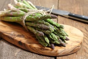 a bundle of fresh cut asparagus on a wooden cutting board