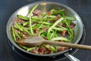 prosciutto and asparagus being sauteed in a pan