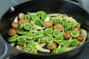 fiddleheads in a pan with italian sausages and onions in a cast iron pan