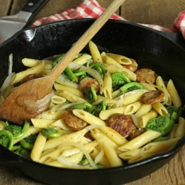 a simple fiddlehead and sausage penne pasta in a cast iron pan