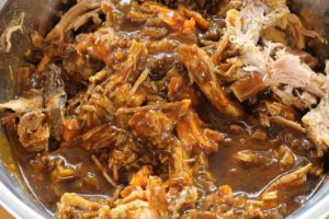 mixing the bbq sauce in with the shredded pork shoulder to make instant pot pulled pork