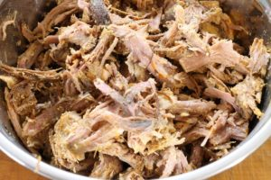 Pork shoulder shredded in a steel bowl