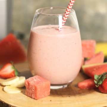 A glass of creamy strawberry banana smoothie on a wooden board