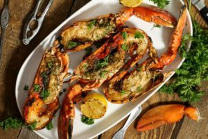 four grilled lobsters garnished with fresh herbs on a white platter