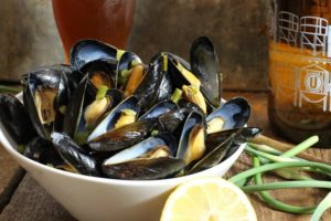A bowl of beer steamed mussels with garlic scapes and lemon on a wooden table surrounded by various ingredients