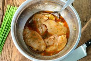 chicken breasts marinating in a metal bowl