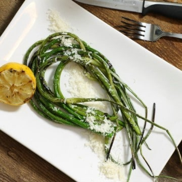 Grilled garlic scapes with grilled lemon and parmesan on a white plate