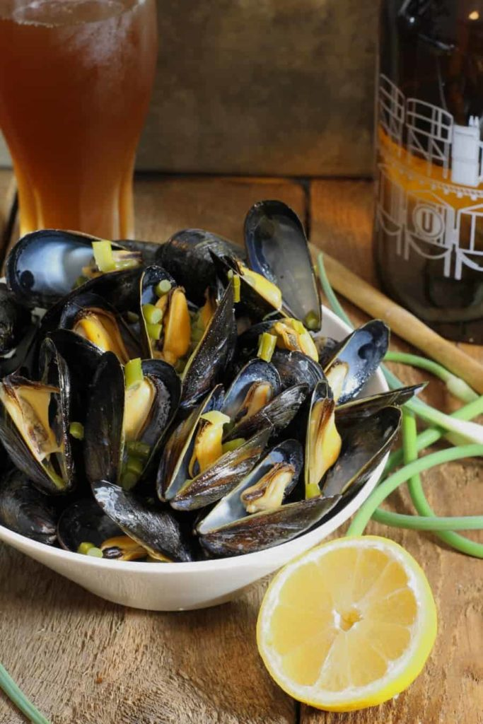 A vertical image of beer steamed mussels tossed with garlic scapes and lemon served in a white bowl