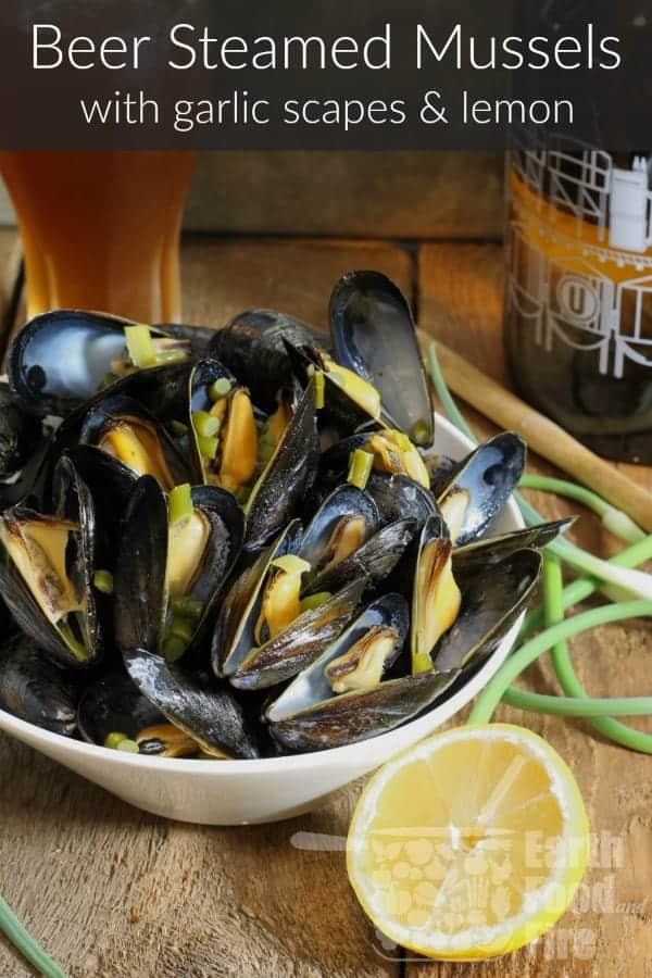 Beer steamed mussels with garlic scapes and lemon served in a white bowl