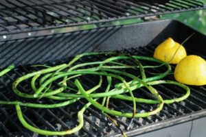 garlic scapes being grilled on a hot BBQ