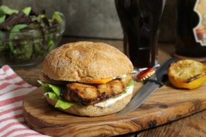 a fully assembled marinated grilled chicken burger on a wooden serving board