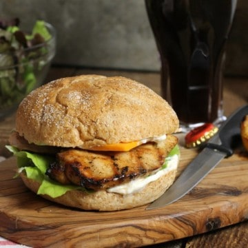 a fully assembled marinated grilled chicken burgermon a wooden serving board
