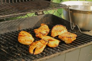 marinated chicken breasts grilling on a BBQ