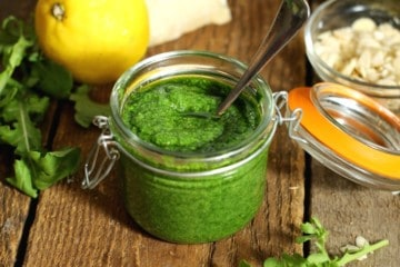 Toasted almond and arugula pesto in a mason jar surrounded by various ingredients